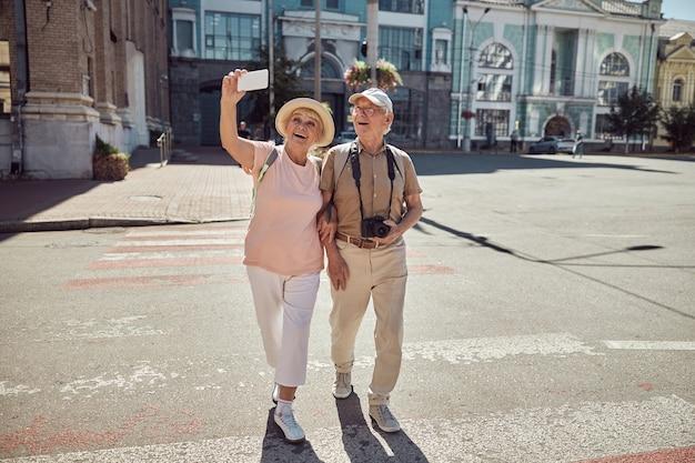 Vrolijke oude vrouw die zichzelf en haar man fotografeert met een smartphone op het zebrapad