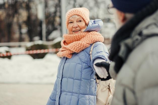 Vrolijke oude vrouw in winterkleren die met haar man loopt en glimlacht terwijl ze zijn hand vasthoudt