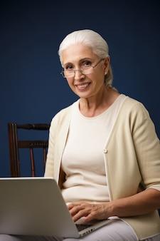 Vrolijke oude vrouw met behulp van laptopcomputer.