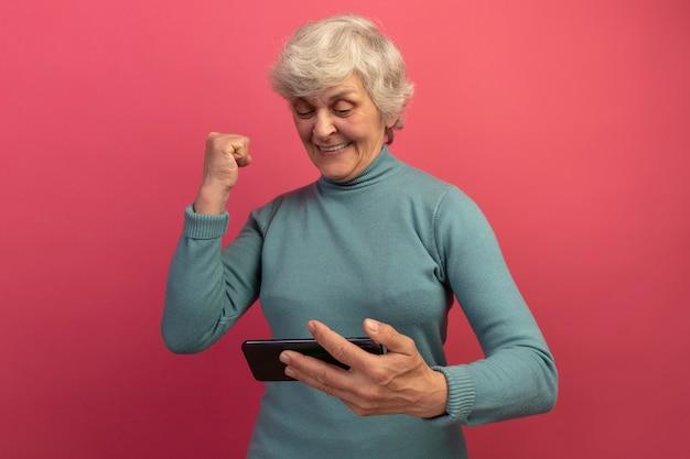 Vrolijke oude vrouw met een blauwe coltrui die een mobiele telefoon vasthoudt en naar een ja-gebaar kijkt