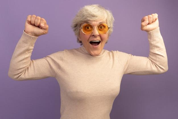 Vrolijke oude vrouw met een romige coltrui en een zonnebril die naar de voorkant kijkt en ja gebaar doet geïsoleerd op een paarse muur purple