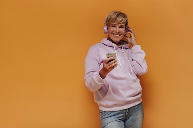 Vrolijke oude vrouw met stijlvol blond kapsel en lila koptelefoon in trendy roze hoodie en spijkerbroek glimlachend en smartphones vast te houden.
