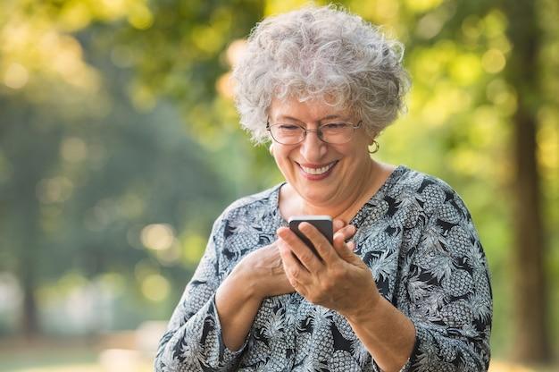 Vrolijke oude vrouw opgewonden bij het ontvangen van goed nieuws via smartphone