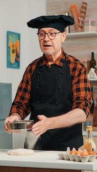 Vrolijke oudere man die het recept stap voor stap opneemt in de keuken van de schoffel. gepensioneerde blogger-chef-beïnvloeder die internettechnologie gebruikt om te communiceren, bloggen op sociale media met digitale apparatuur