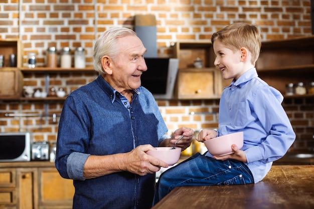 Vrolijke oudere man granen eten tijdens het ontbijt met zijn kleinzoon