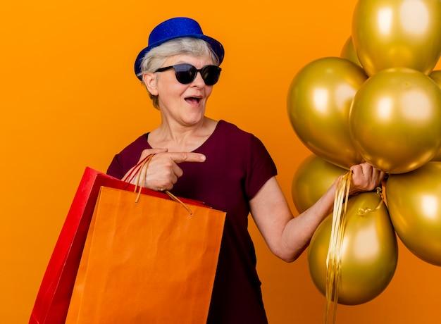 Vrolijke oudere vrouw in zonnebril met feestmuts houdt helium ballonnen en papieren boodschappentassen geïsoleerd op oranje muur met kopie ruimte