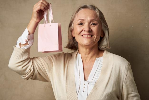 Vrolijke oudere vrouw met cadeautas vakantiestudio
