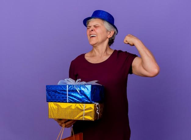 Vrolijke oudere vrouw met feestmuts houdt geschenkdoos en gespannen biceps geïsoleerd op paarse muur met kopie ruimte