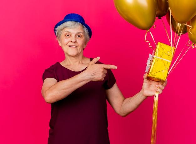 Vrolijke oudere vrouw met feestmuts houdt helium ballonnen en wijst op geschenkdoos op roze
