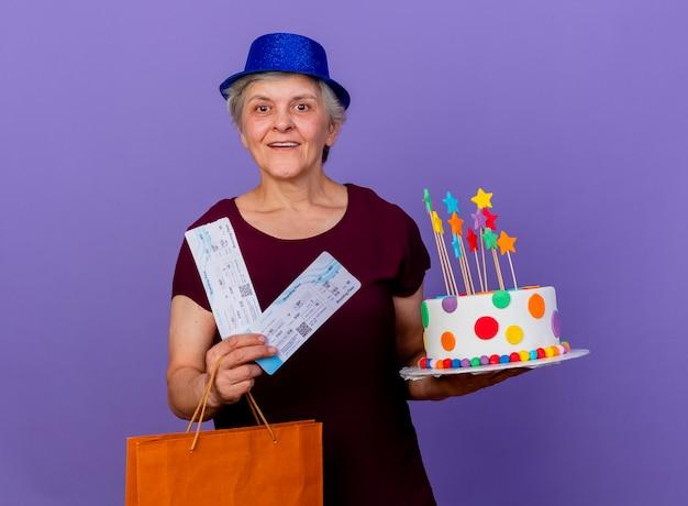 Vrolijke oudere vrouw met feestmuts houdt papieren boodschappentas voor vliegtuigtickets en verjaardagstaart geïsoleerd op paarse muur met kopie ruimte