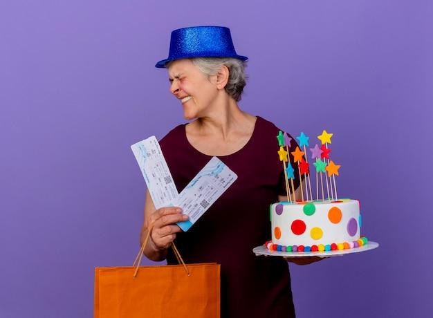 Vrolijke oudere vrouw met feestmuts houdt papieren boodschappentas voor vliegtuigtickets en verjaardagstaart kijken naar kant geïsoleerd op paarse muur met kopie ruimte