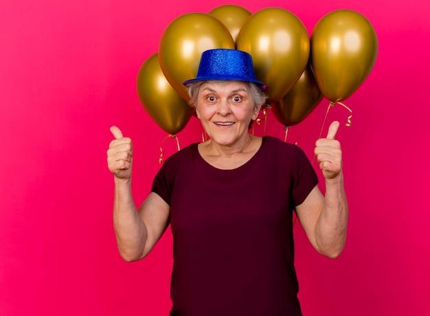 Vrolijke oudere vrouw met feestmuts staat voor helium ballonnen en duimen omhoog met twee handen op roze