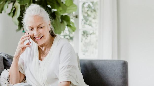 Vrolijke oudere vrouw praten op een telefoon op een bank