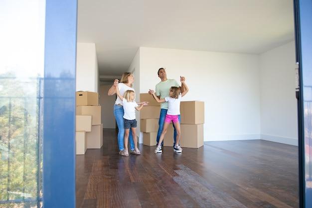 Vrolijke ouders en dochters die dansen en plezier hebben in de buurt van hopen dozen terwijl ze naar een nieuwe flat verhuizen