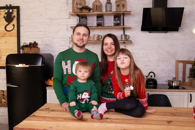 Vrolijke ouders en hun schattige dochter meisje en babyjongen thuis wachten op kerstmis