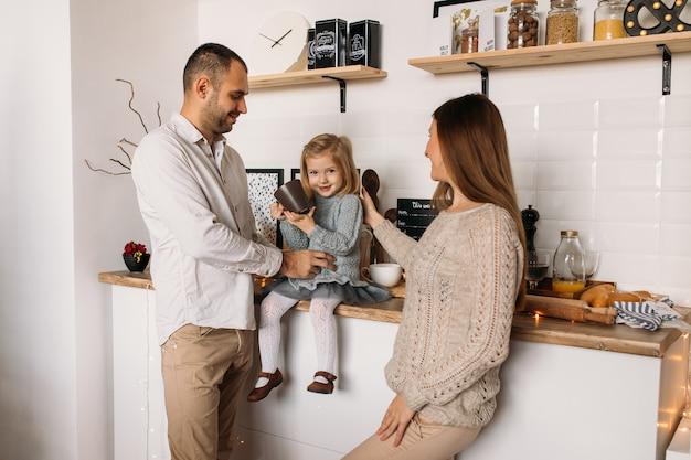 Vrolijke ouders en hun schattige dochter meisje in keuken thuis.