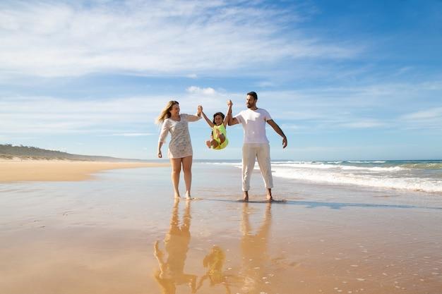Vrolijke ouders en meisje genieten van wandelen en activiteiten op het strand, kind ouders hand in hand, springen en benen overgeven