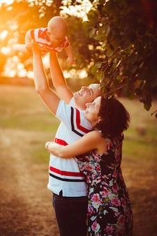 Vrolijke ouders houden hun kleine zoon omhoog in de buitenkant te staan