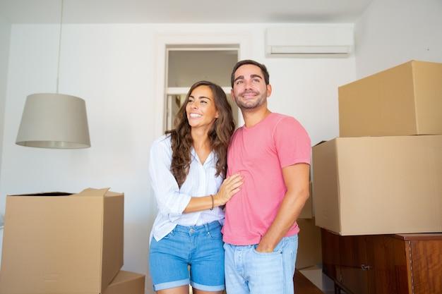 Vrolijke paar kijken uit over hun nieuwe appartement, wandelen tussen kartonnen dozen en knuffelen