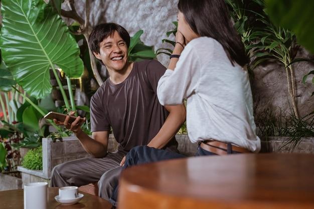 Vrolijke paar lachen zittend in een coffeeshop wanneer ze een slimme telefoon vasthouden