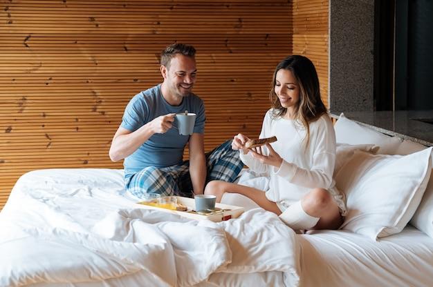 Vrolijke paar ontbijten op bed