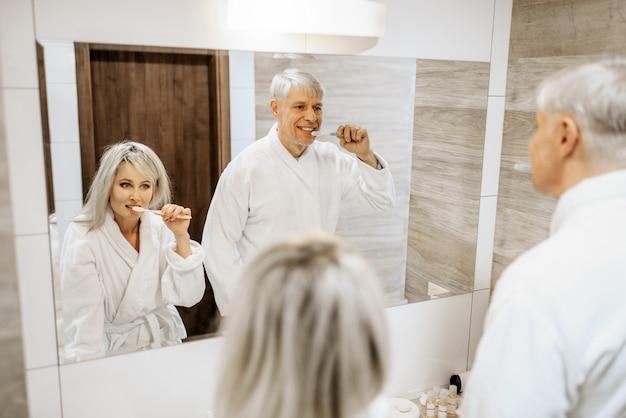 Vrolijke paar tandenpoetsen bij de spiegel in de badkamer. grijsharige volwassen man en vrouw in badjassen thuis in de ochtend