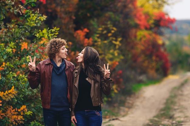 Vrolijke paar toont emoties man en vrouw in leren jassen en spijkerbroek tonen elkaar tongen tegen van herfst bomen