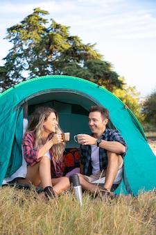 Vrolijke paar zitten in tent, chatten en thee drinken. gelukkige wandelaars ontspannen op het gazon, kamperen en genieten van de natuur. reizigers buiten in de natuur. toerisme, avontuur en zomervakantie concept