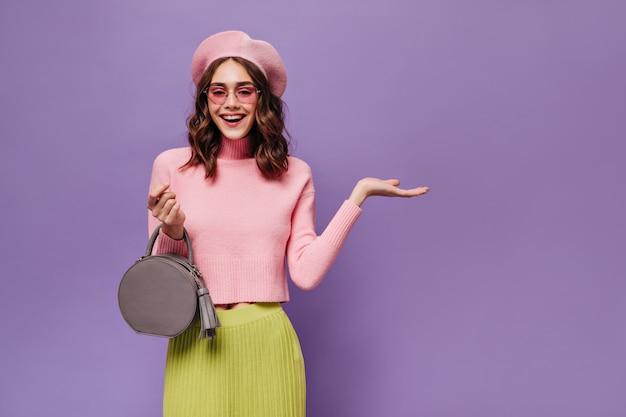 Vrolijke parijse vrouw in baret en zonnebril wijst op plaats voor tekst op paarse muur