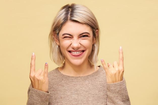 Vrolijke parmantige stijlvolle vrouw steekt tong uit en knippert, maakt duivelshoorns gebaar, toont universeel heavy metal bord voor you rock, vertegenwoordigd door wijsvinger en pink omhoog