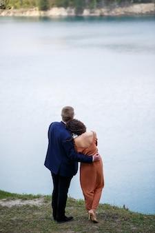 Vrolijke pasgetrouwden gaan hand in hand en lachen, tegen de achtergrond van een meer en een groene weide. vrolijke bruidegom en mooie bruid met krullend haar lopen in de wei