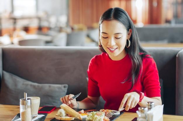 Vrolijke pauze. jonge aantrekkelijke stijlvolle zakenvrouw geniet van haar pauze tijdens het eten in restaurant
