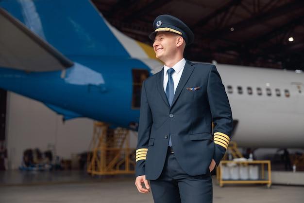 Vrolijke piloot in uniform glimlachend weg, staande voor groot passagiersvliegtuig in luchthavenhangar. vliegtuigen, beroep, transportconcept