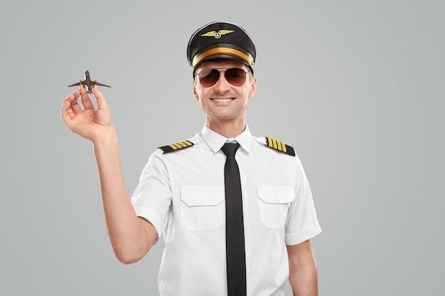 Vrolijke piloot in uniform met speelgoedvliegtuig