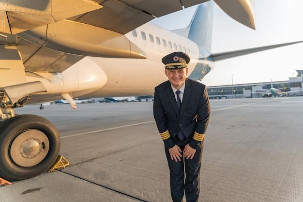 Vrolijke piloot poseert onder de vleugel van een vliegtuig