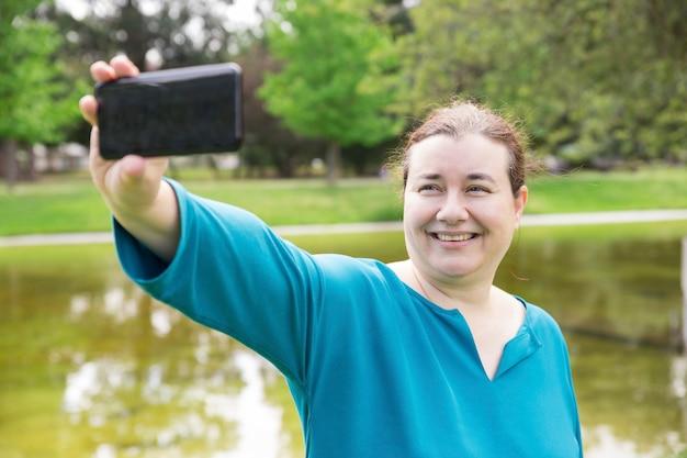 Vrolijke plus gerangschikte vrouw die selfie in park nemen