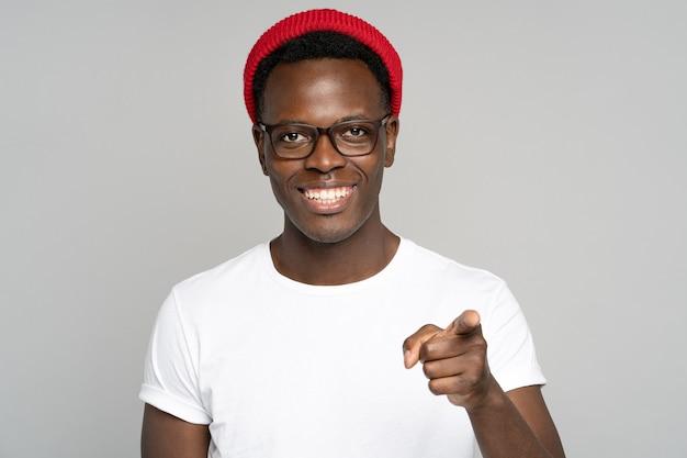 Vrolijke positieve afro hipster man breed glimlachend, wijst met een vinger naar je, studio grijze achtergrond