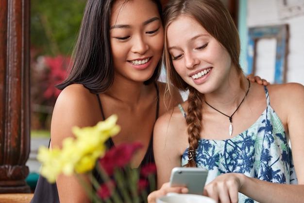 Vrolijke positieve aziatische en blanke vrouwen hebben blije uitdrukkingen, brengen samen tijd door, bekijken video in blog op smartphone