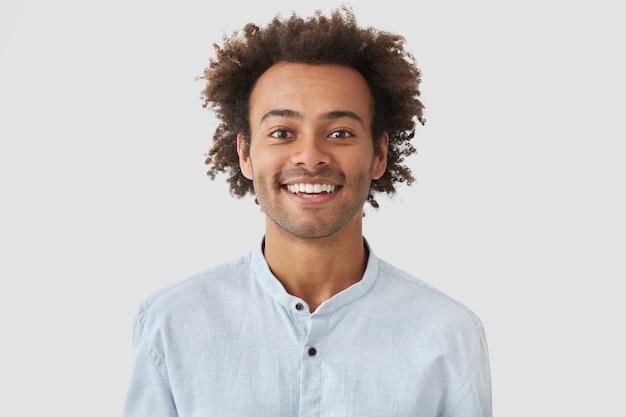 Vrolijke positieve blije man heeft een brede glimlach, verheugt zich over promotie op het werk