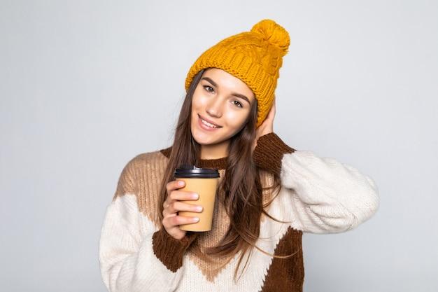 Vrolijke positieve cafeïnevrouw, vrouw in een sweater en een hoed met koffie in haar handen die op een witte muur stellen