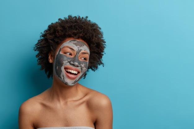 Vrolijke positieve donkere gekrulde vrouw staat naakt binnen, past een moddermasker van schoonheid toe voor een perfecte zachte gezichtshuid, geeft om de teint, kijkt graag weg, geïsoleerd op een blauwe muur.