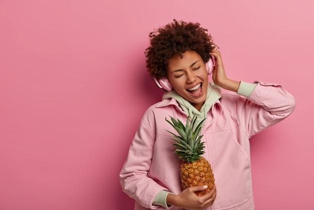 Vrolijke positieve etnische vrouw luistert aangename muziek in hoofdtelefoons