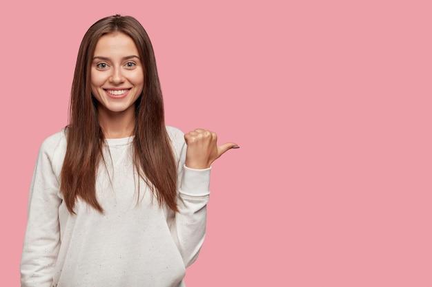 Vrolijke positieve jonge europese vrouw met donker haar, brede stralende glimlach, wijst met duim opzij