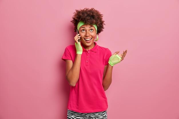 Vrolijke positieve krullende haired tienermeisje heeft telefoongesprek