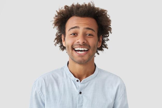 Vrolijke positieve man met mooie lach, breed lacht of grinnikt, voelt zich geweldig en dolgelukkig