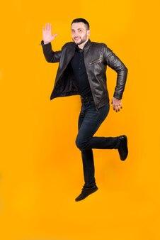 Vrolijke positieve man sprong op oranje
