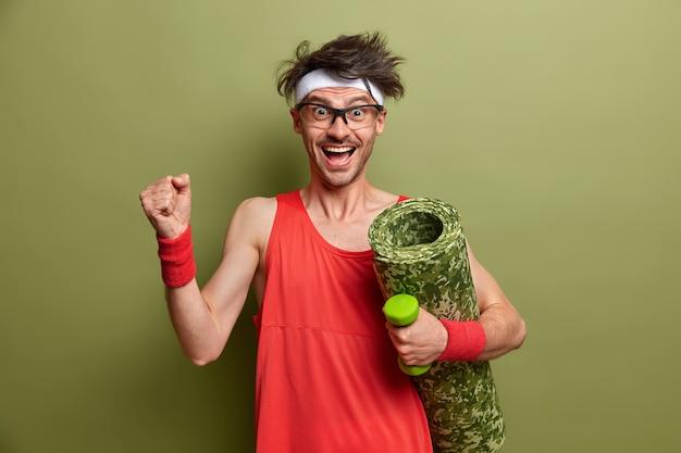 Vrolijke positieve man traint met dumbbell, heft arm op en balt vuist, draagt karemat, heeft als doel om fitness gespierd lichaam krachtig en sterk te laten voelen, gekleed in rood shirt, hoofdband, polsbandjes