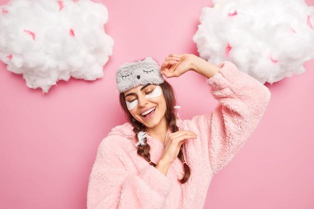 Vrolijke positieve meid wordt wakker in een goed humeur, heft armen op en glimlacht zachtjes