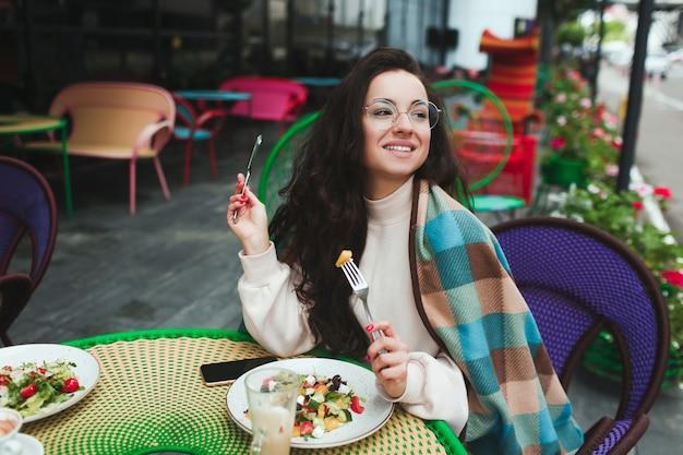Vrolijke positieve mooie vrouw die lunch eet
