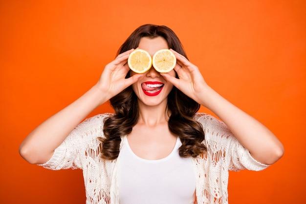 Vrolijke positieve schattige mooie mooie prachtige vrouw likt haar bovenlip op zoek naar twee citroenen als een verrekijker.